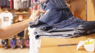 Woman Shopping for Denim Jeans Shorts in Clothing Store