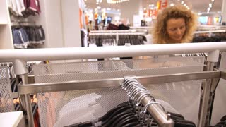 Woman Shopping for Garment in Clothing Store