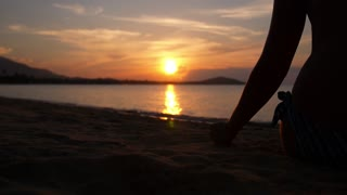 Woman Silhouette Pours Sand at Beach against Sunset. Slow Motion.