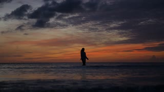 Woman Silhouette Walking on Seashore at Sunset in Sea