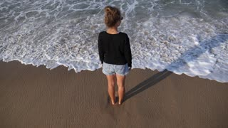 Woman Standing in Sea Waves on the Beach