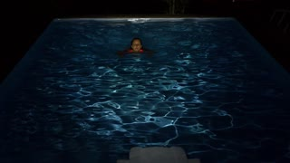 Woman Swims in the Swimming Pool at Night. Slow Motion.