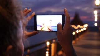 Woman Taking Night View Photos Using Mobile Phone