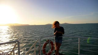 Woman Texting in a Smart Phone on the Ferry with the Sea and Sunrise in the Background. Slow Motion.