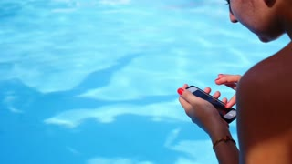 Woman Texting SMS on her Mobile Phone on the Beautiful Blue Poolside during Holiday.