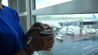 Woman Traveler with Coffee Cup Waiting for Flight in Airport