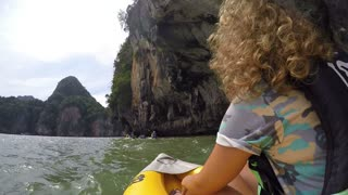 Woman Traveling in Boat Tour Looking at Cliff and Cave in Sea