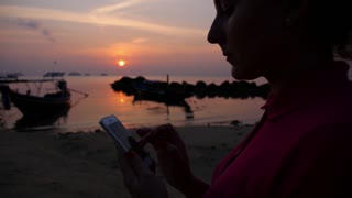 Woman Using her Mobile Phone on the Beach against Sunset.
