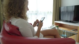 Woman Using Phone Sitting on Couch Indoors