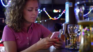 Woman Using Smart Phone in Bar Counter Drinking Beer