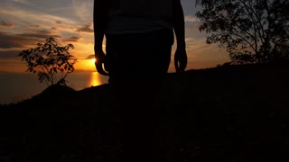 Woman Walking Against Sunset over the Sea. Slow Motion.