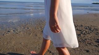 Woman Walking on the Sea Coast at Sunset