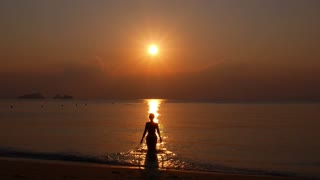 Woman Walking Towards Sunset in the Sea. Slow Motion.