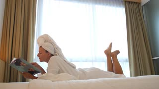 Woman with a Magazine Lying on Bed in Bathrobe