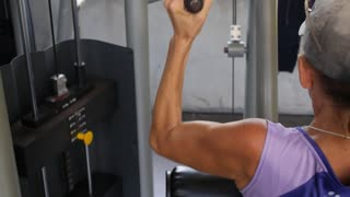 Woman Workout, Building Muscles on Fitness Machine in Gym