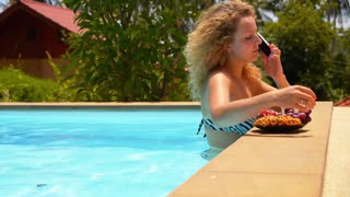 Young Beautiful Woman Talking on Cell Phone and Eating Pineapple in Pool.