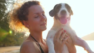 Young Beautiful Woman with Cute Dog on the Beach. Slow Motion.