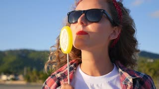 Young Blonde Woman with Curly Hair Licks Lollipop