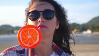 Young Brunette Woman with Curly Hair Licks Lollipop