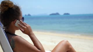 Young Cheerful Woman Talking by Phone on a Beach