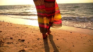 Young Curly Woman Walking on Beach in Long Dress against Sunset. Slow Motion.