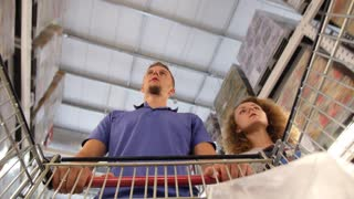 Young Family Couple Choosing Food in Supermarket