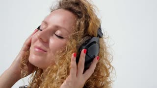 Young Female Relaxing in Headphones Listening Music. Slow Motion.