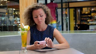 Young Female Texting Message on Cell Phone in Cafe