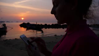 Young Female Using Mobile Phone on Tropical Beach at Sunset. Slow Motion.