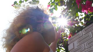 Young Girl in Sun Beams Looking at Flowers Outdoors. Slow Motion.
