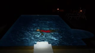 Young Girl Swims in the Pool at Night. Slow Motion.