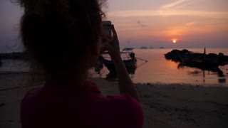 Young Girl Taking Photos Of Sea Sunset With Mobile Smart Phone