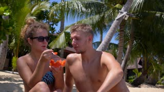 Young Happy Couple Eating Fruits at the Beach