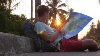 Young Man with Backpack Planning Road Trip with Map.
