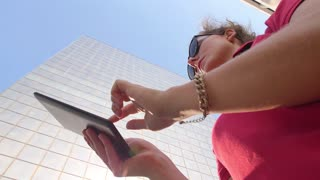 Young Urban Hipster Female Using Tablet in City