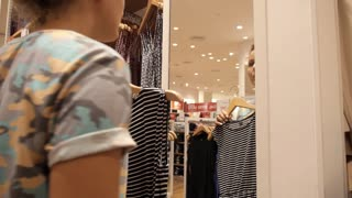 Young Woman Choosing Clothes in Showroom while Shopping