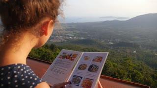 Young Woman Choosing from a Restaurant Menu Outdoors