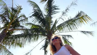Young Woman Dancing on Background of Palm Trees. Slow Motion.