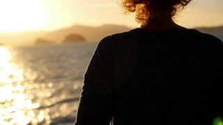Young Woman Dreaming against Imressive Sunset. Golden Sunshine Glow Sparkle on the Sea Surface.