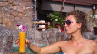 Young Woman Drinking Fruit Juice in Swimming Pool