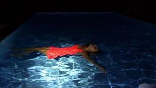 Young Woman in Bright Dress Lying on the Pool Water at Night.
