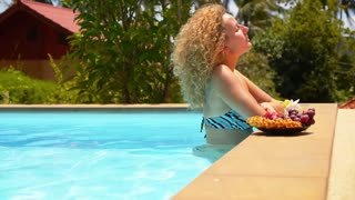 Young Woman in the Swimming Pool Eating Fresh Fruits.