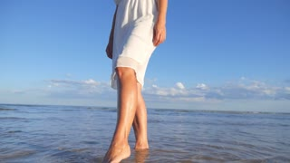Young Woman in White Dress Walking Alone at Beach