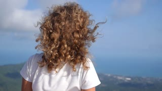 Young Woman Looking at Sea from Top of Mountain