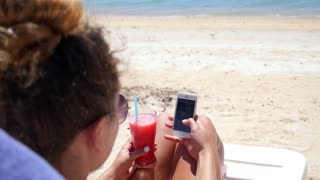 Young Woman on Beach with Mobile Phone