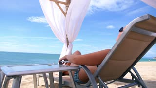 Young Woman on Lounge at Beach Enjoying Vacation