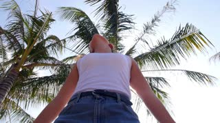 Young Woman on the Beach Dancing against Palm Tree. Slow Motion.