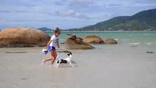 Young Woman Playing with Dog on Beach