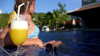 Young Woman Resting in Swimming Pool on Sunny Day with Cocktail.