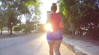Young Woman Running on a Rural Road at Sunset. Slow Motion.
